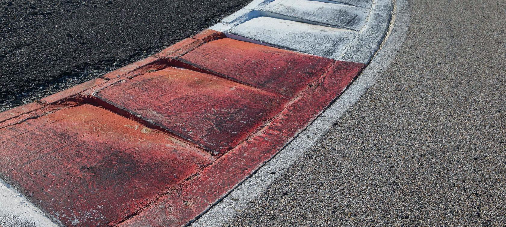 Kurve einer asphaltierten Straße mit weiß-rotem Seitenstreifen