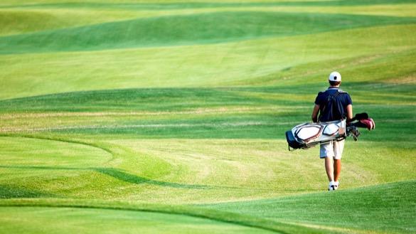 Mann von hinten mit Golfbag laufend über Green.