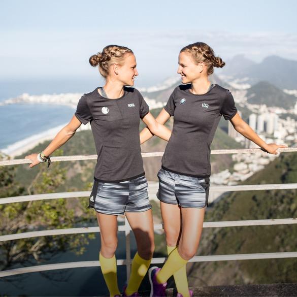 Hahnertwins im Sportoutfit stehend an Geländer, im Hintergrund Berge und Meer