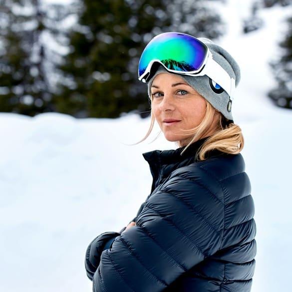 Sandra steht mit Jacke und Mütze sowie Skibrille auf der Stirn vor einer verschneiten Landschaft.