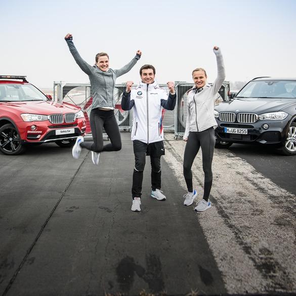 Bruno und Hahnertwins jubelnd vor zwei BMW Fahrzeugen auf Straße.