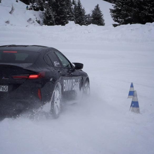 """""""BMW Bank""""-gebrandeter BMW fährt im Schnee an blau-weißen Hütchen vorbei"""