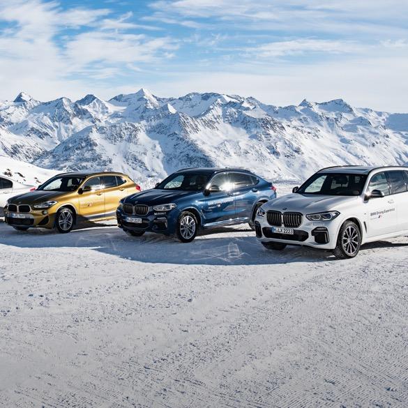 BMW Flotte parkend im Schnee. Im Hintergrund Berge.