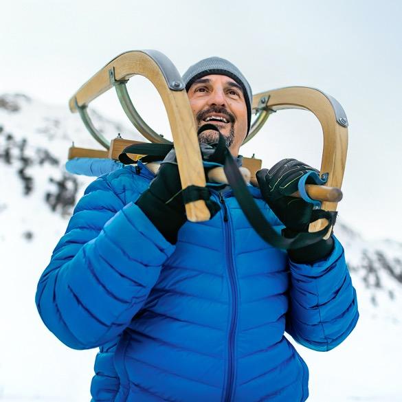 Georg Hackl mit blauer Skijacke und Schlitten auf dem Rücken