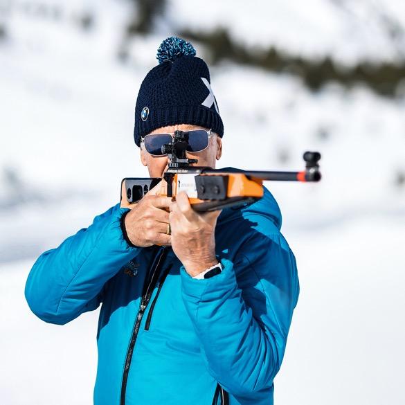 Fritz Fischer mit blauer Skijacke, blauer X Challenge Mütze und Biathlon Gewehr
