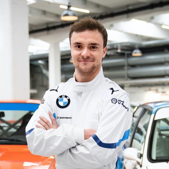 Lucas Auer mit verschränkten Armen vor Classic Cars