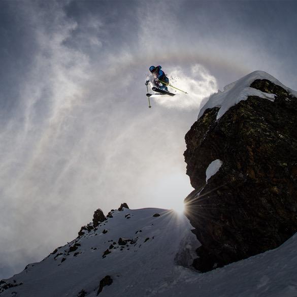 Skifahrer springt von Fels.